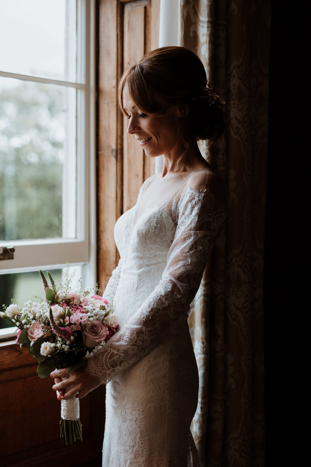 bride standing by the window with her bouquet