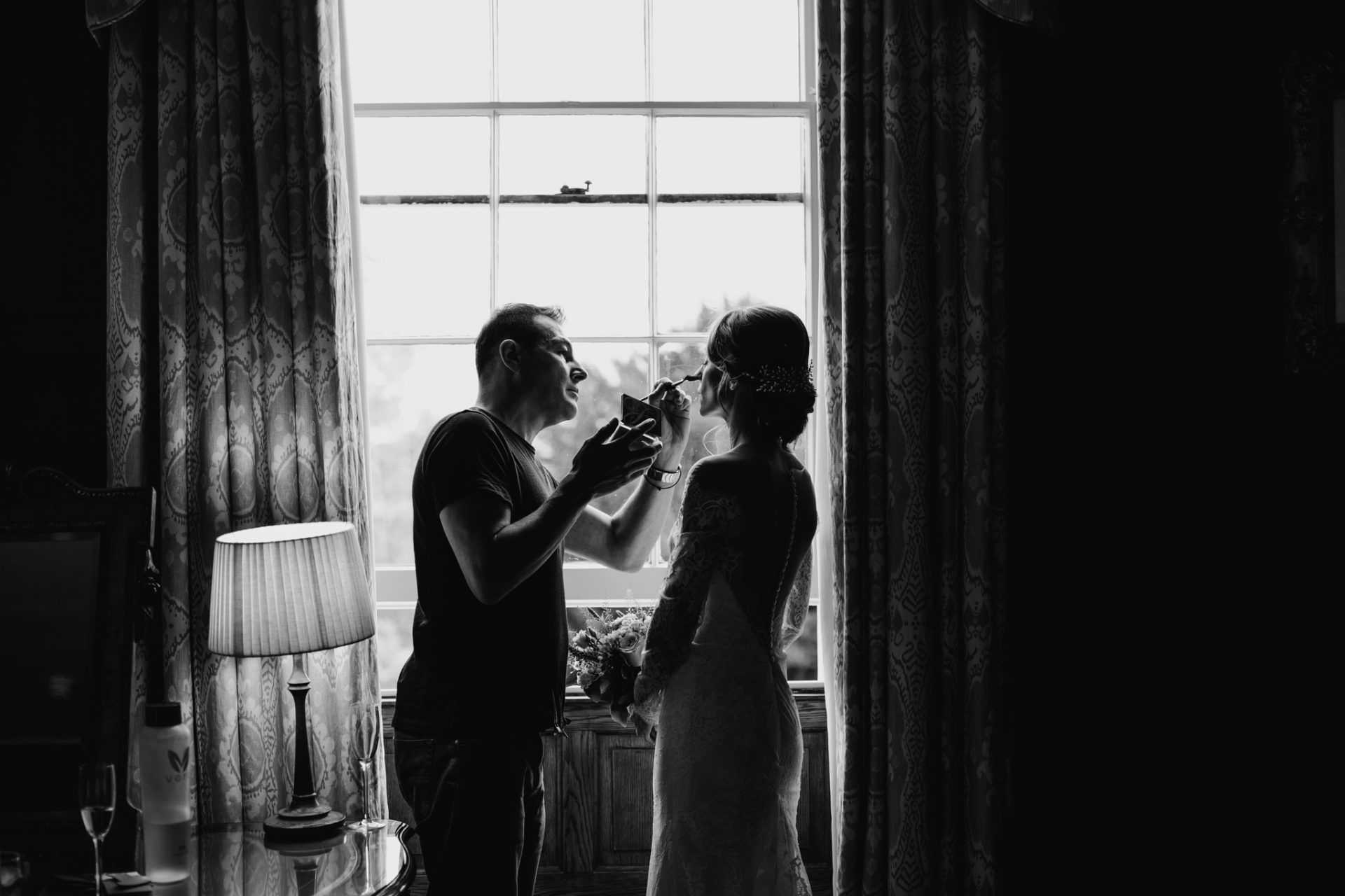 bride having her make up retouched in the window