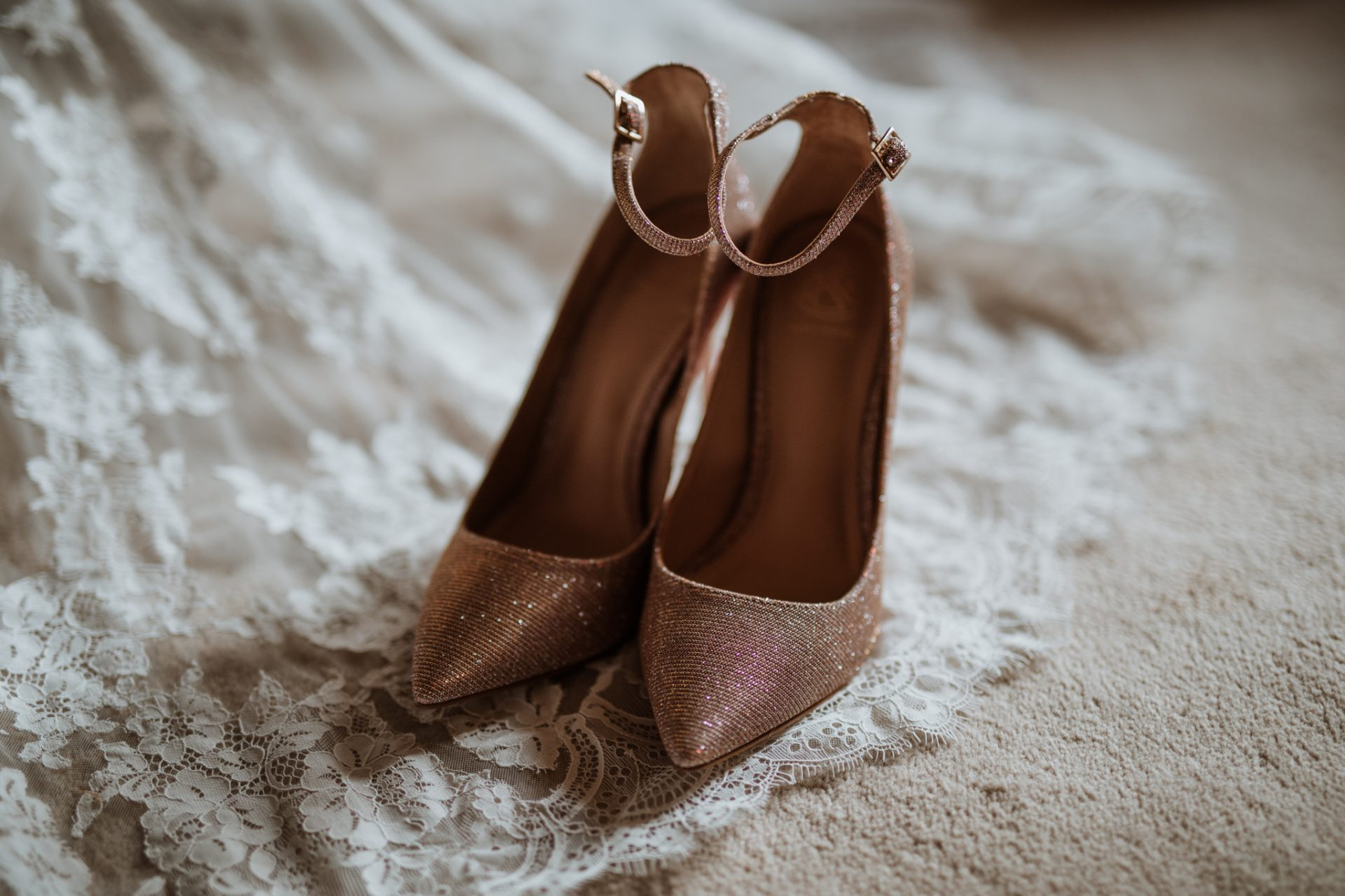 sparkly rose gold wedding shoes on lace wedding dress