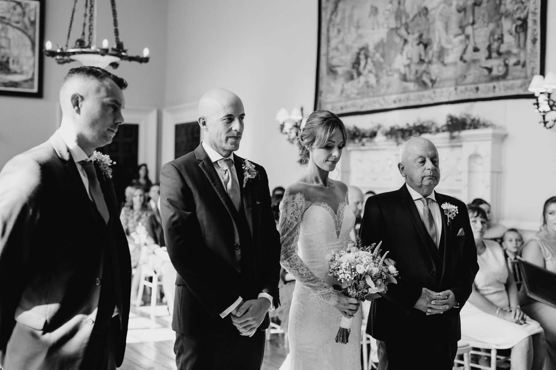best man, groom, bride and father stand during the ceremony