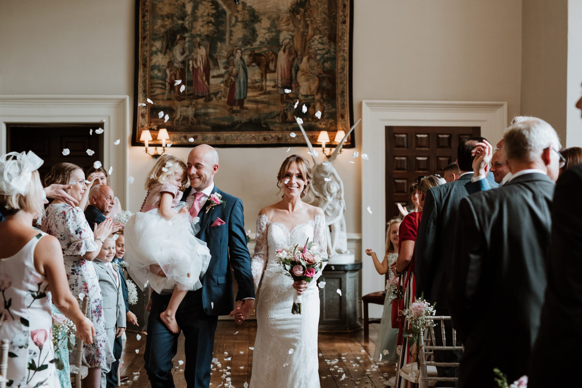 bride and groom walk through confetti tunnel holding daughter