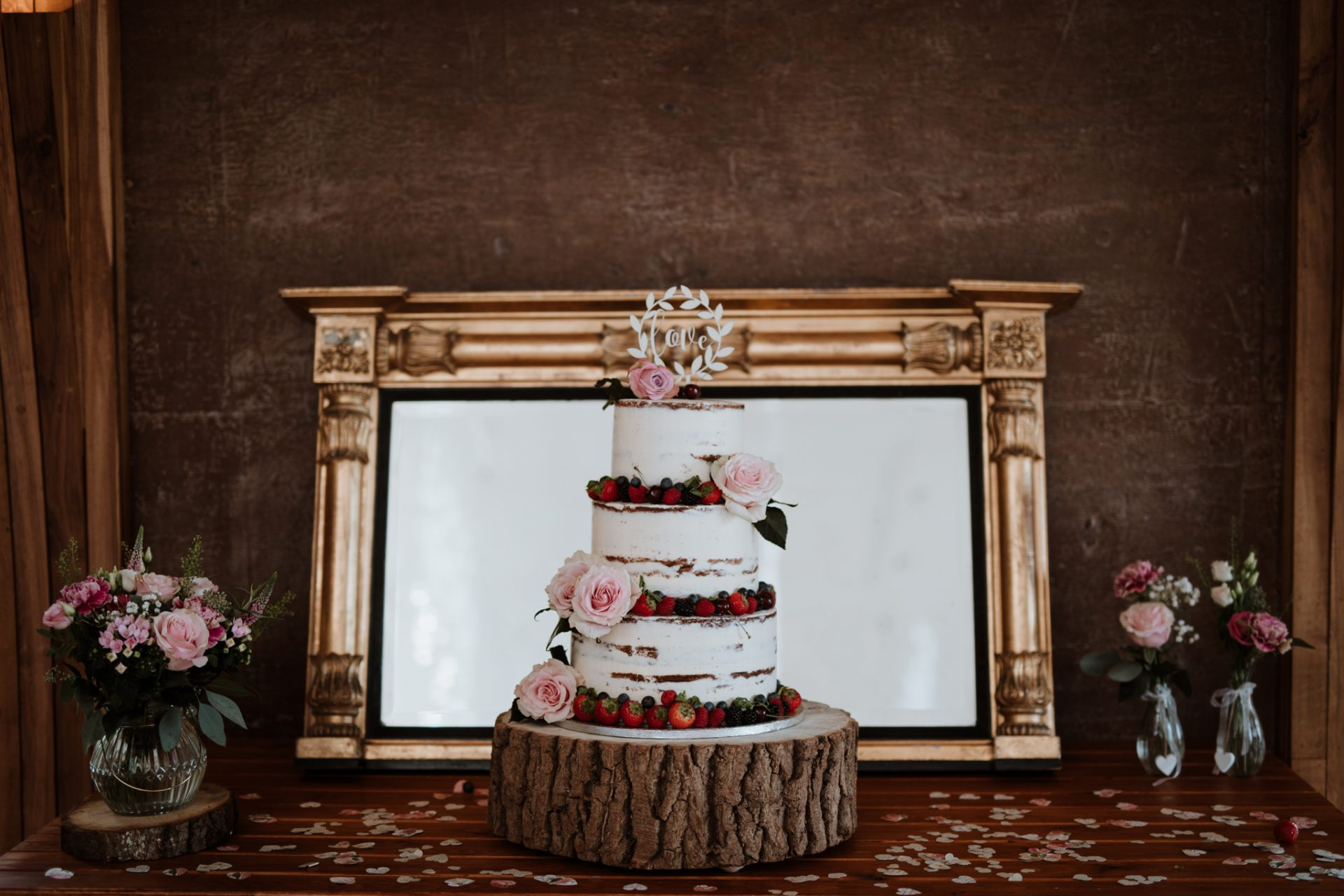 naked wedding cake in front of ornate gold mirror