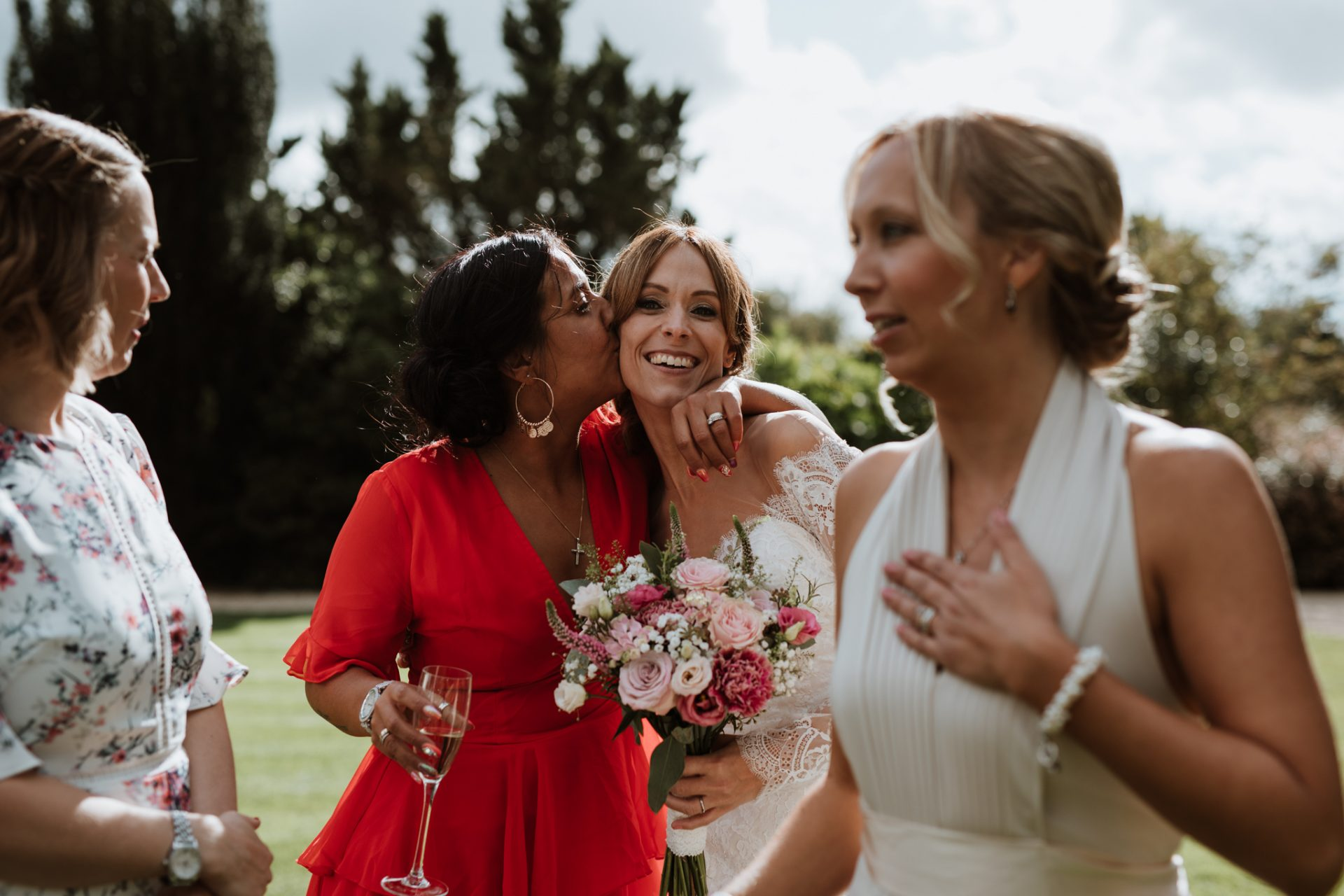 guest kissing bride and cheek