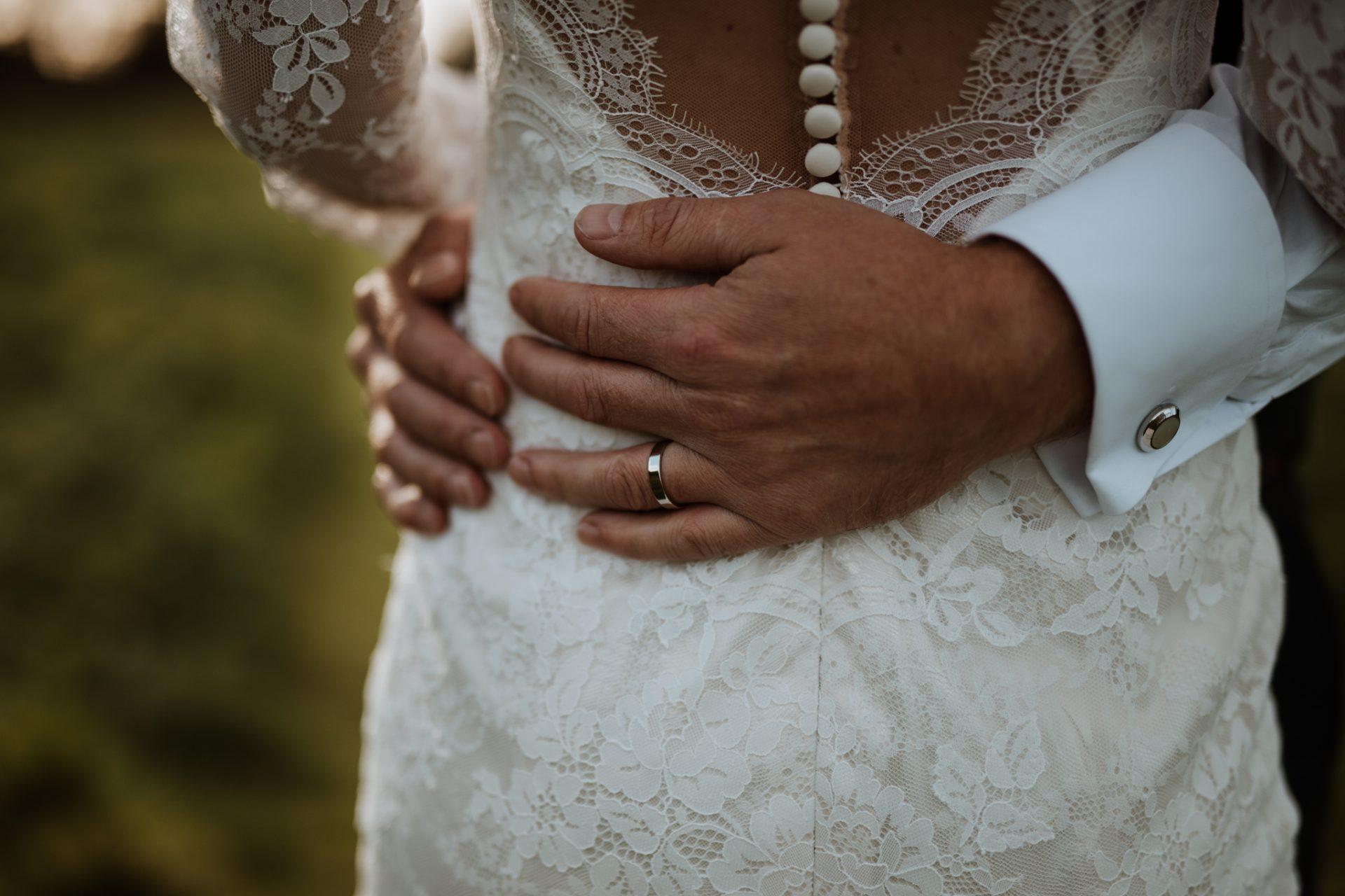 grooms hand and wedding ring around brides waist