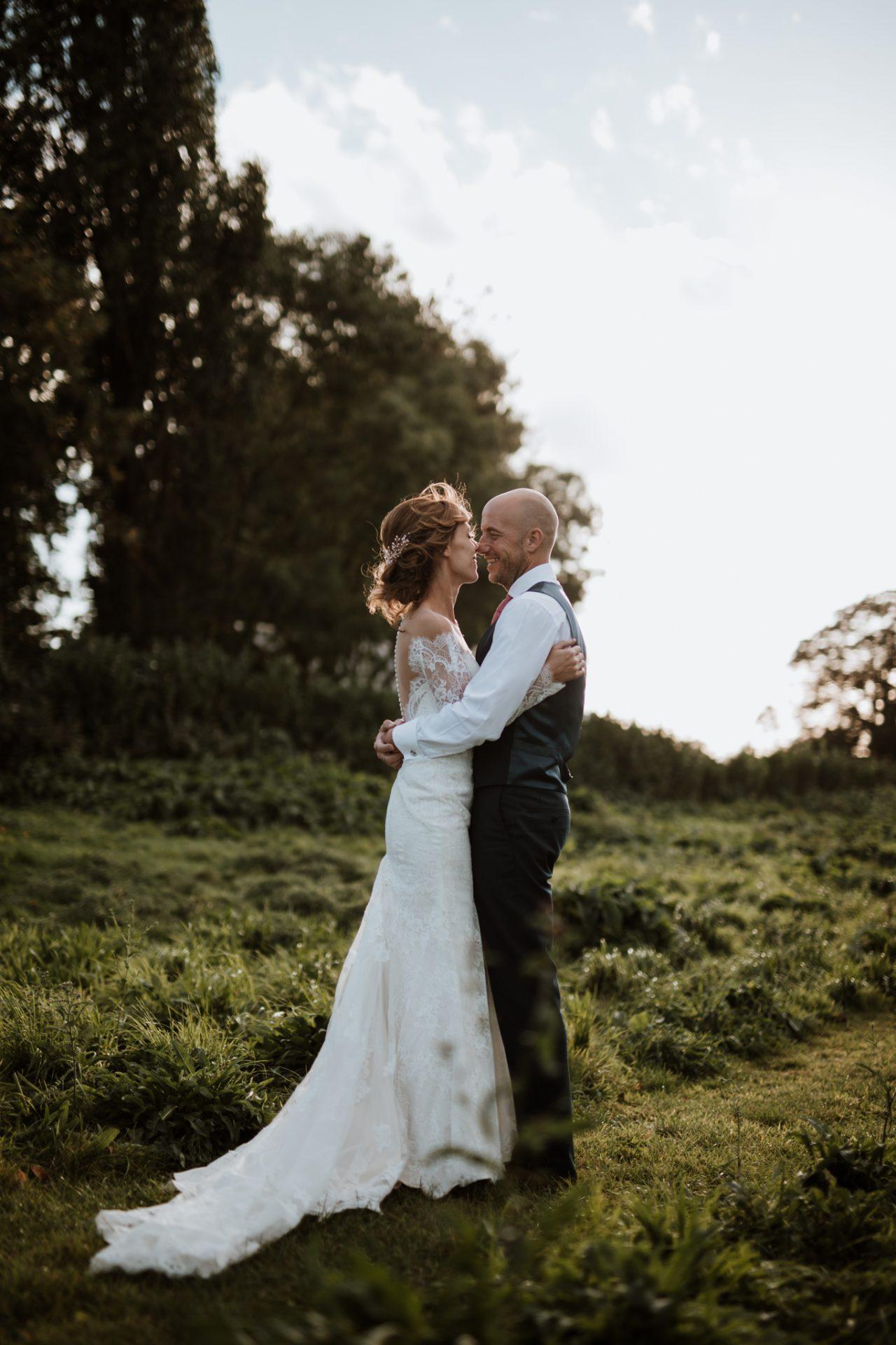 bride and groom hugging golden hour wedding