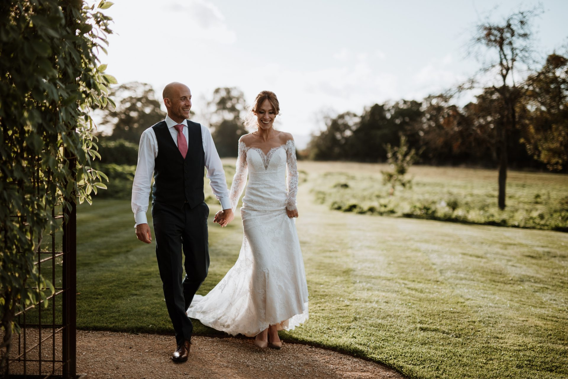 bride and groom walk through sunset