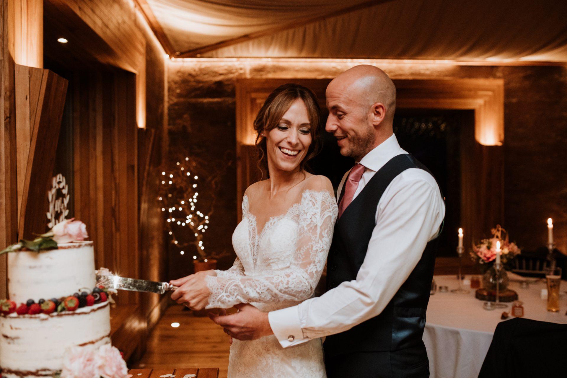 bride and groom cut naked wedding cake