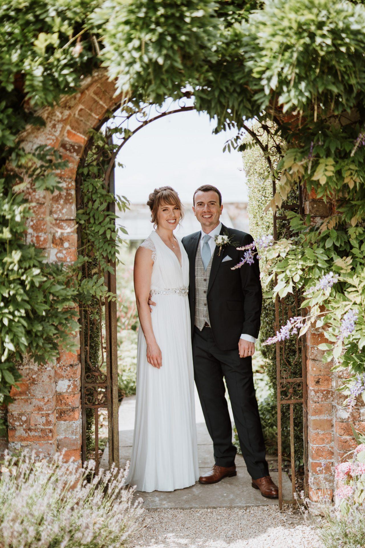 bride and groom smile camera under wisteria archway