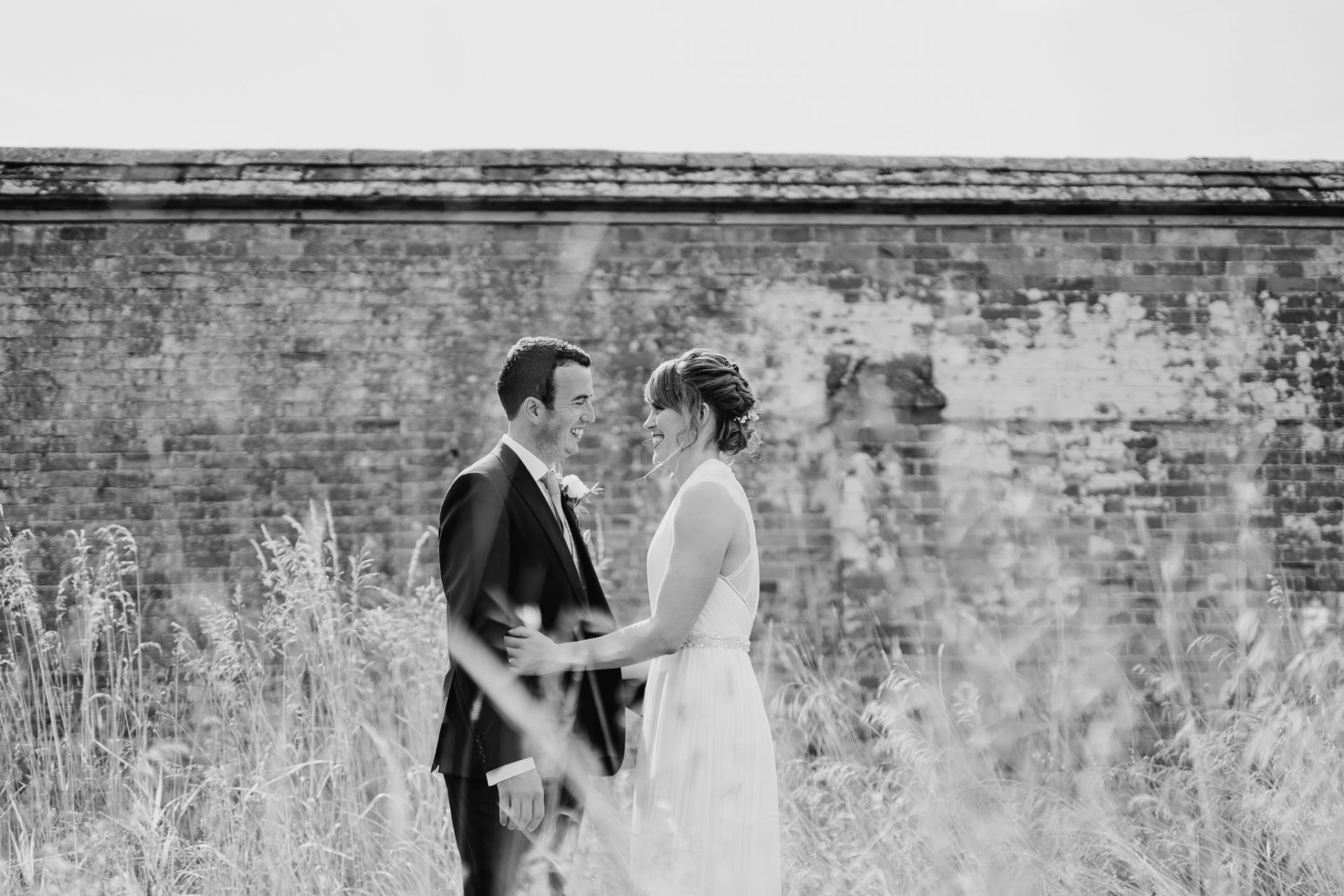 bride groom laughing in front of old brick wall wild flowers