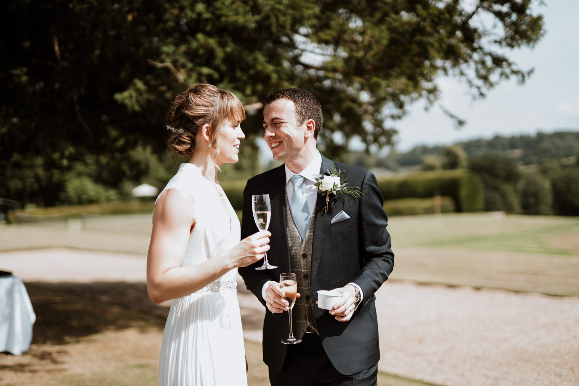 bride and groom laugh naturally with champagne ice cream