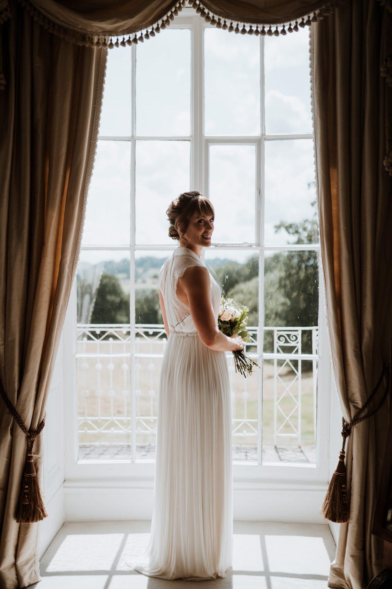 bride full length portrait in french windows