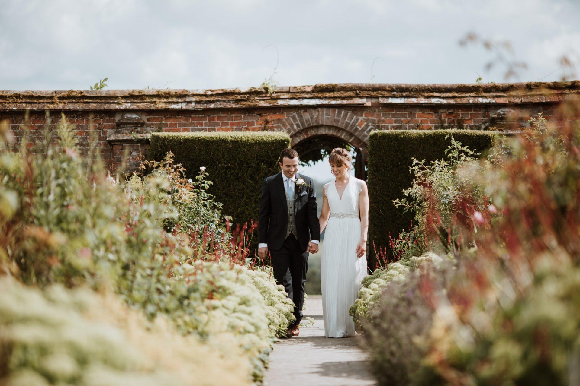 bride and groom walking holding hands through flower garden