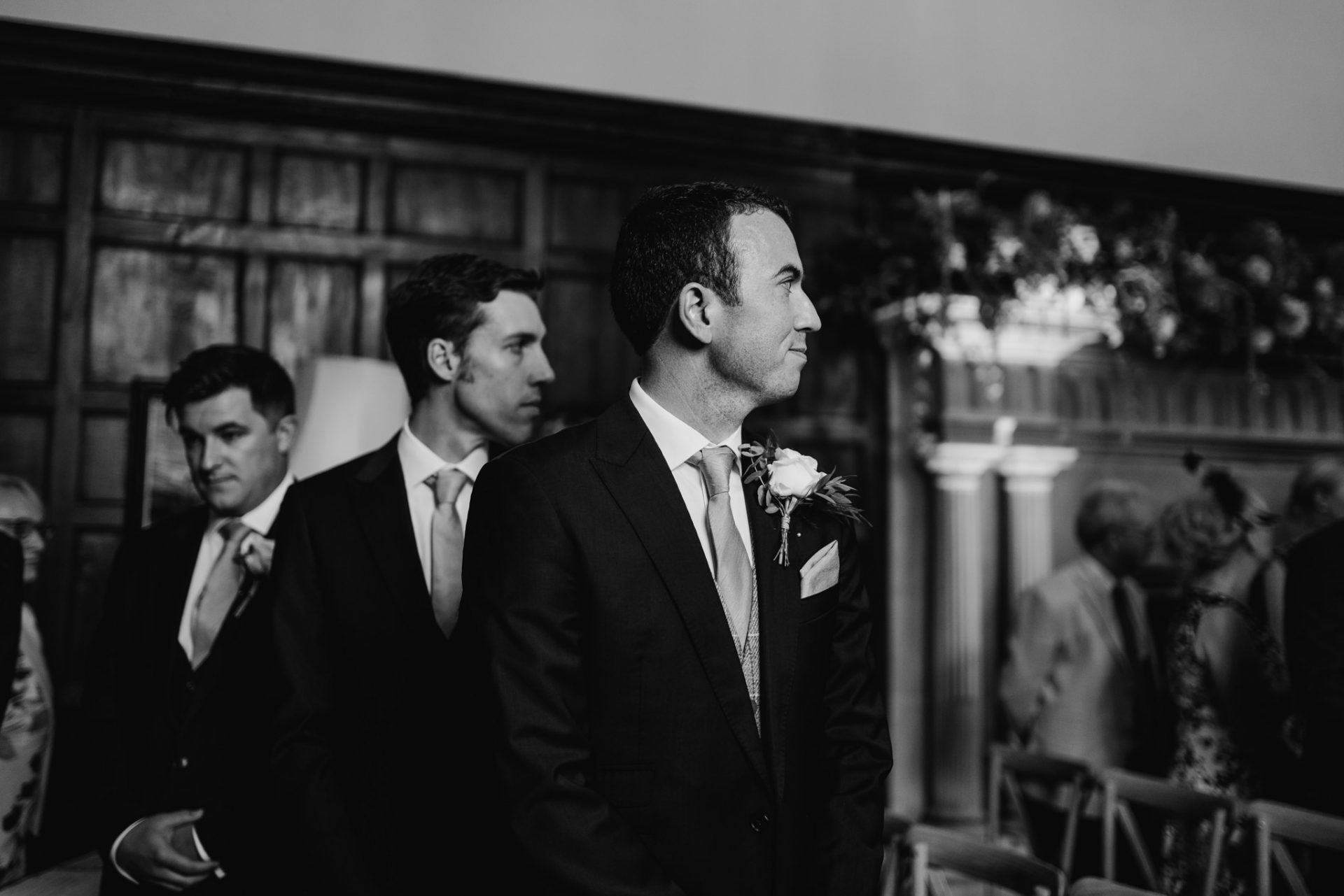grooms face seeing bride walking down the aisle