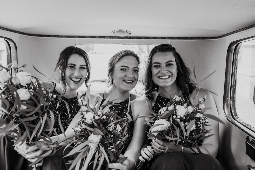bridesmaids in the back of vintage car