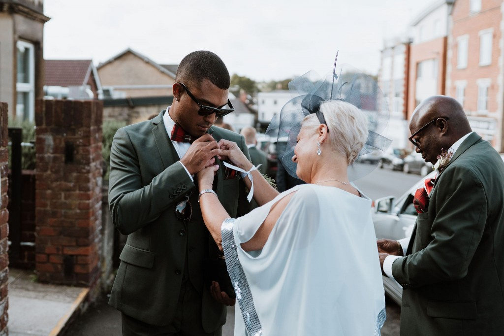mother of the groom helping with the boutonnière