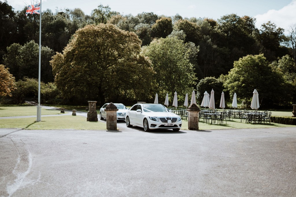 Bride and groom arriving at the Manor House Hotel, Castle Coombe in a Mercedes