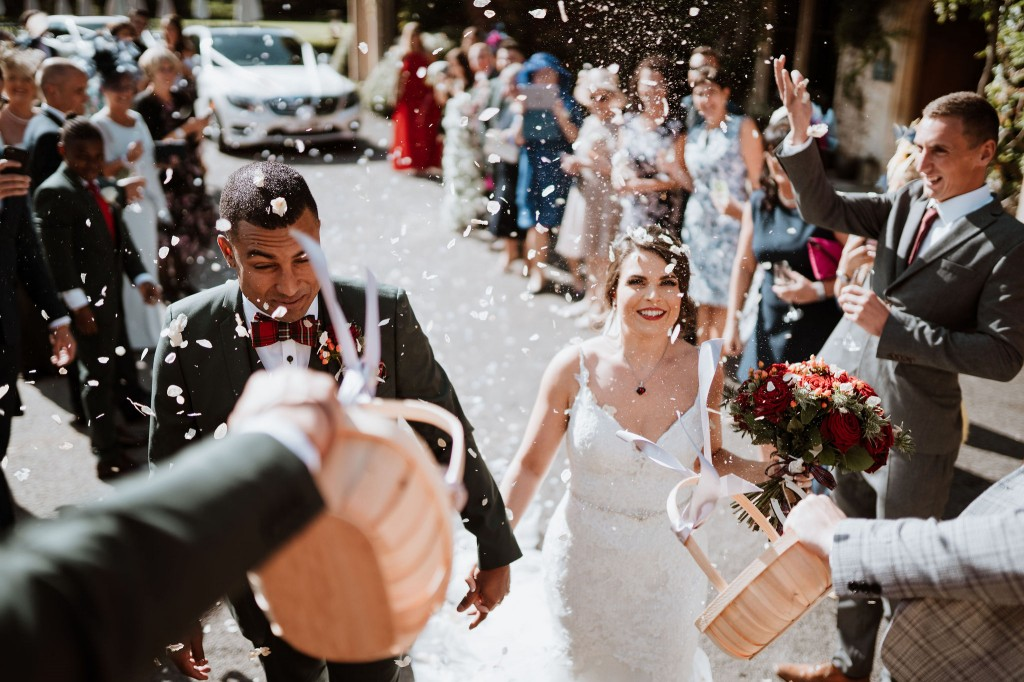 confetti tunnel for the bride and groom outside the manor house hotel, castle coombe