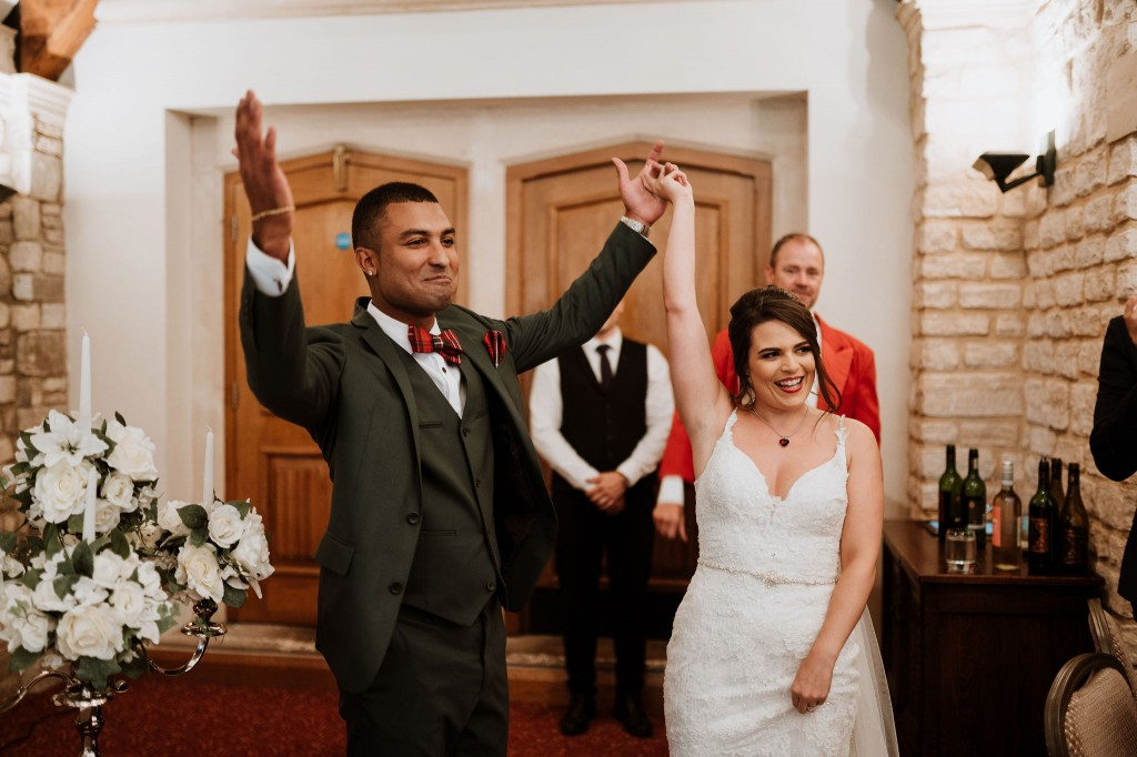 bride and groom cheering after they walk in to the wedding breakfast