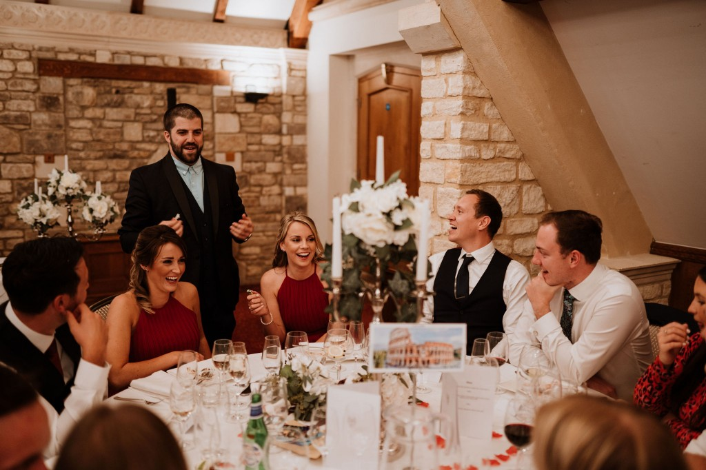 candid photo of wedding guests laughing magician