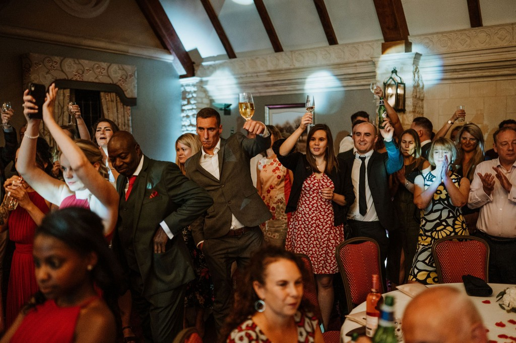 wedding guests cheering bride and grooms first dance