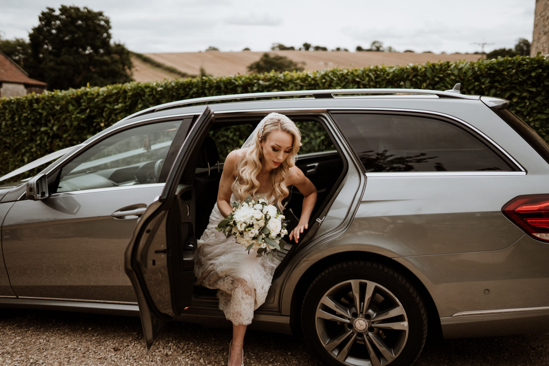bride getting out of mercedes wedding car at Priston Mill