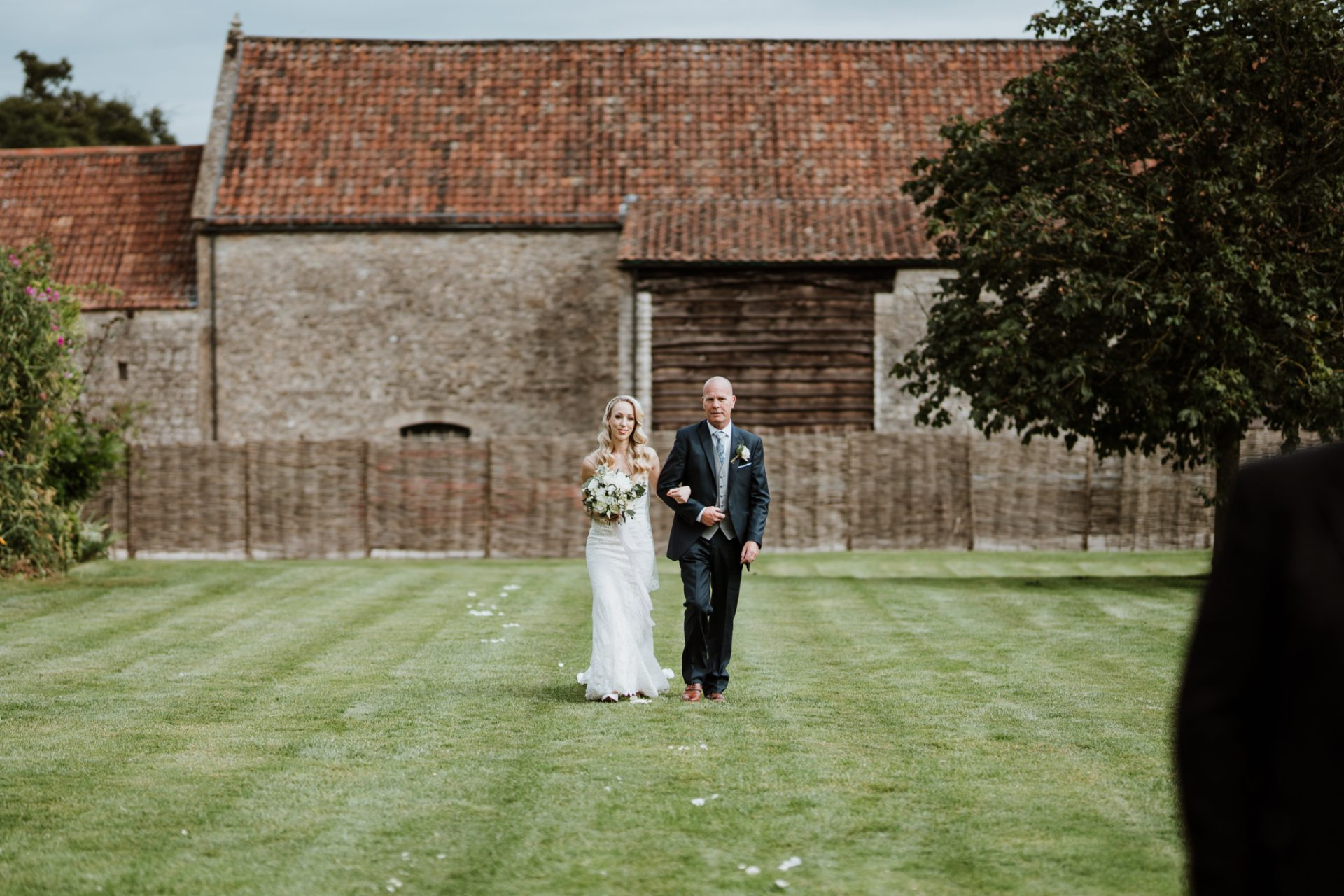 bride and father walking across lawn to outdoor ceremony