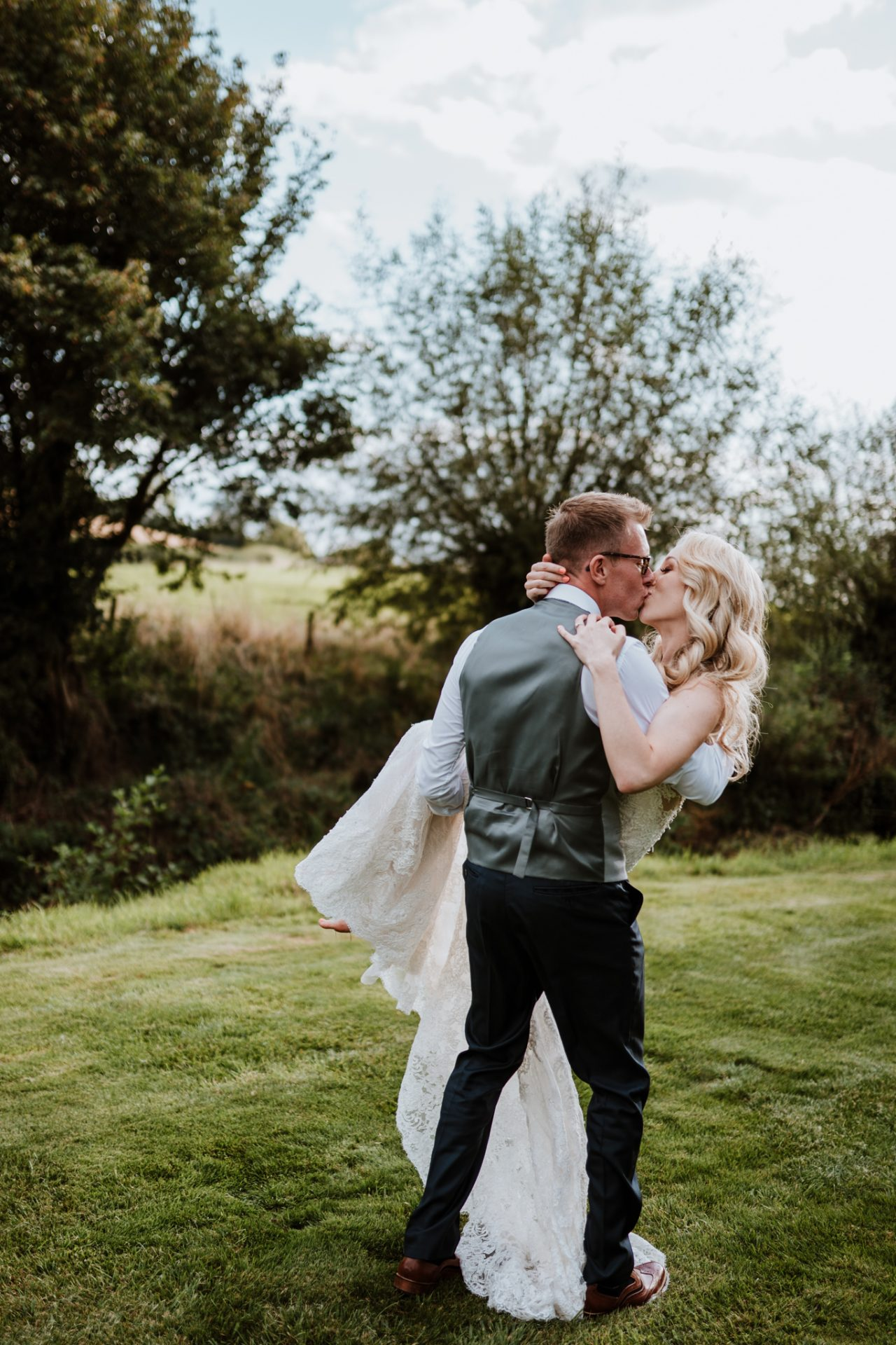 groom carrying bride kissing priston mill