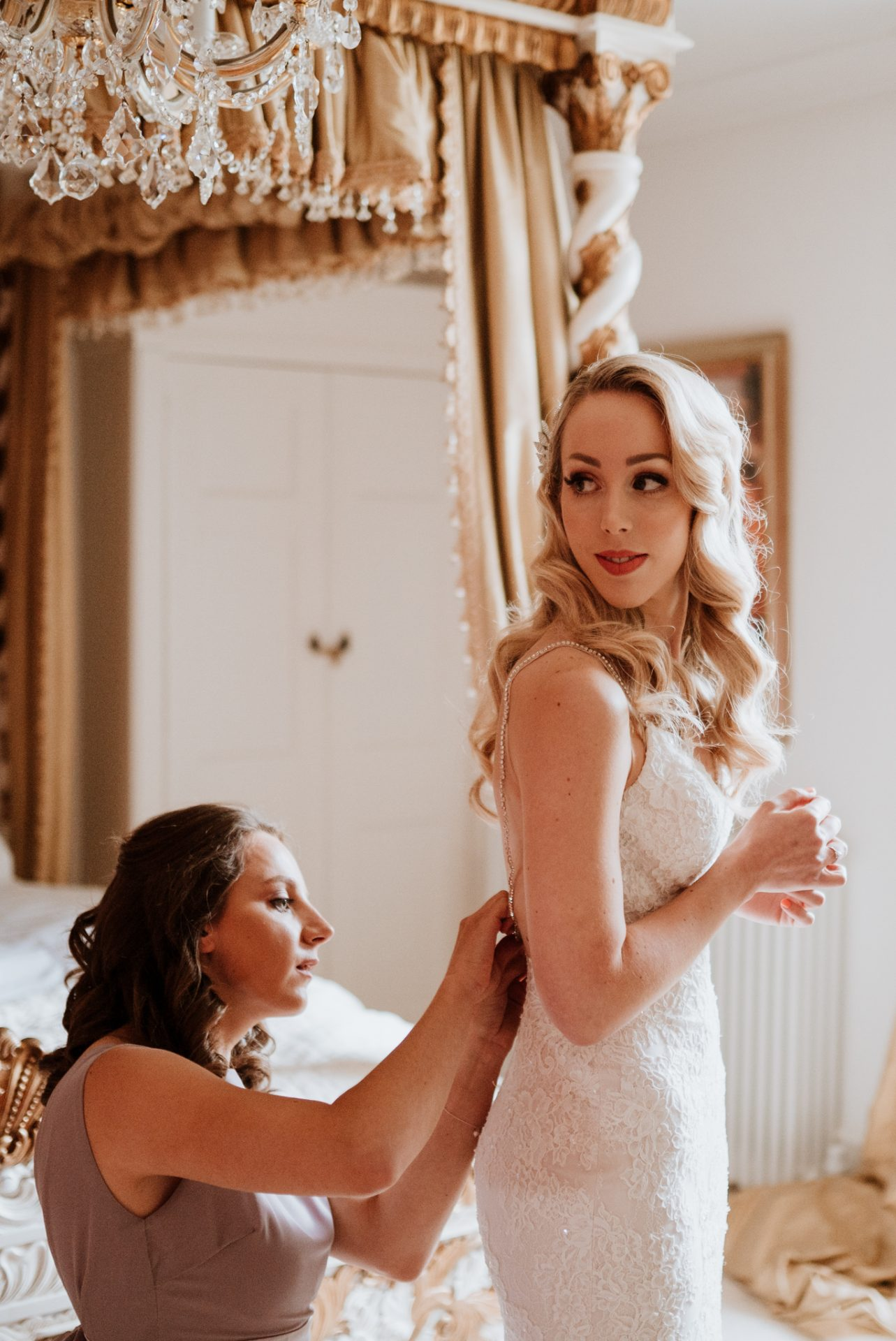 bridesmaid helping the bride in to her wedding dress
