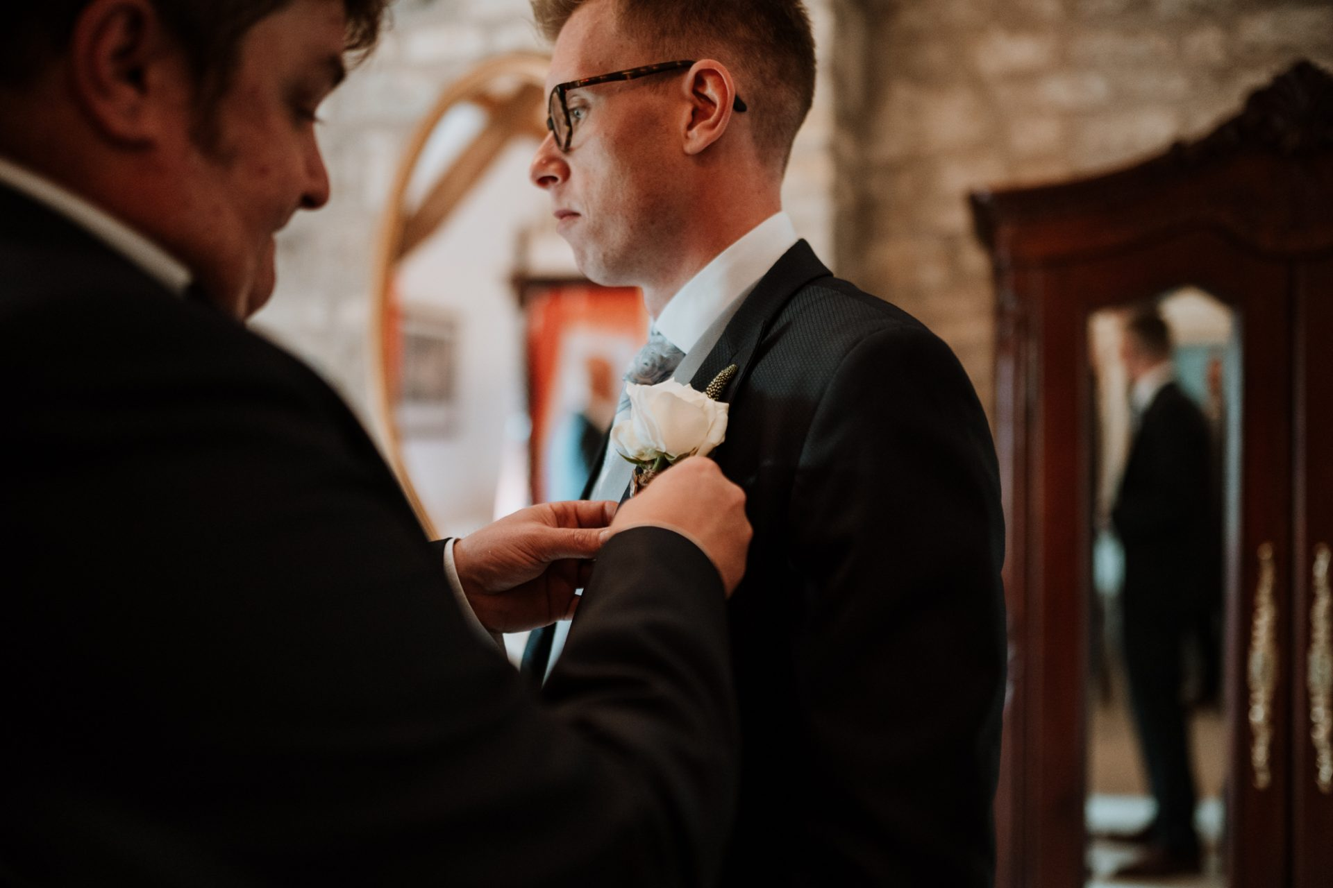groomsman putting in groom's buttonhole