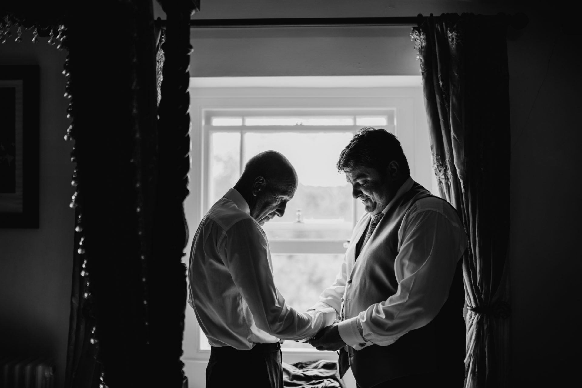 father and best man doing up cufflinks in window
