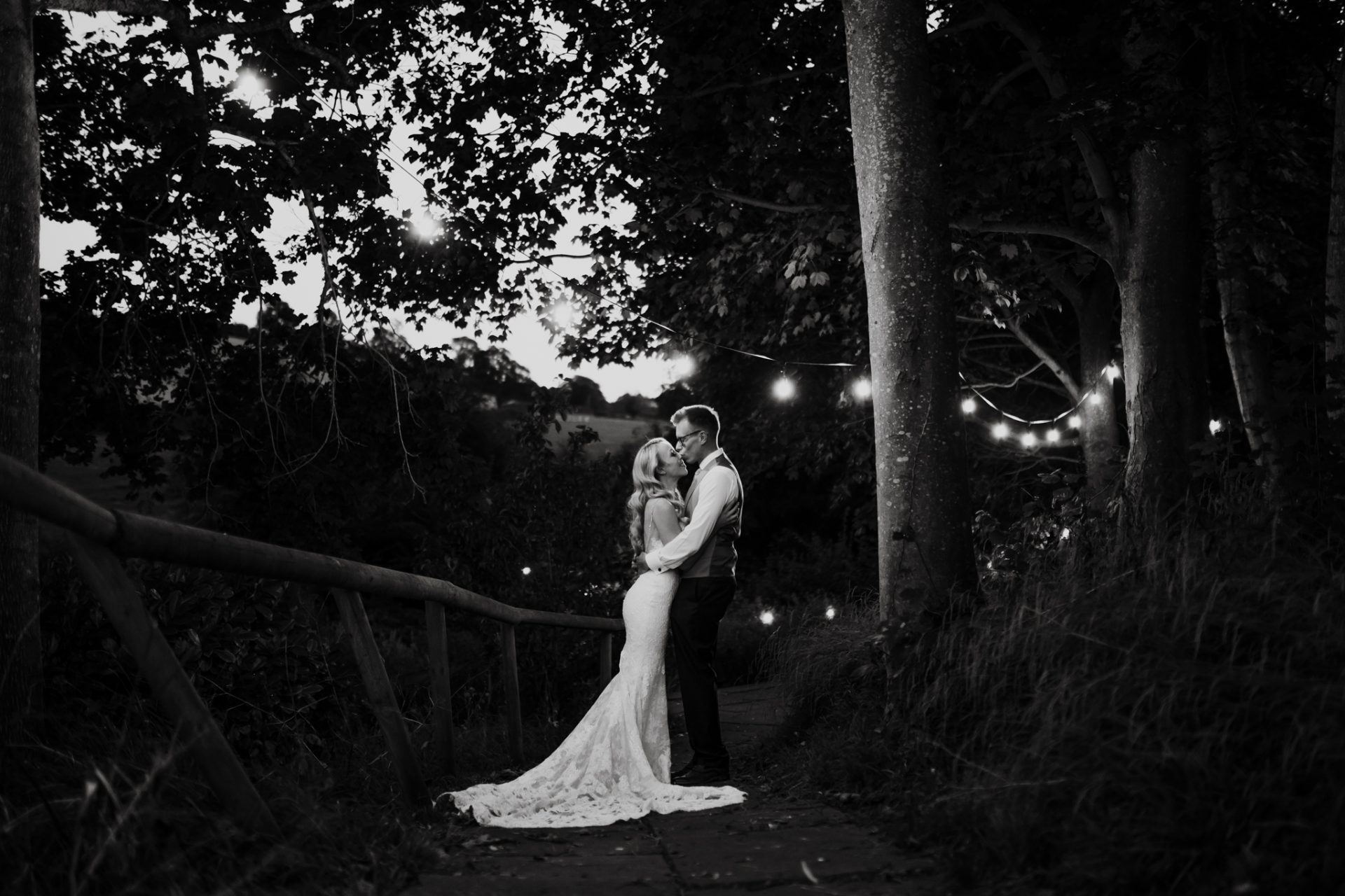 bride and groom outside under string fairy lights at night priston mill
