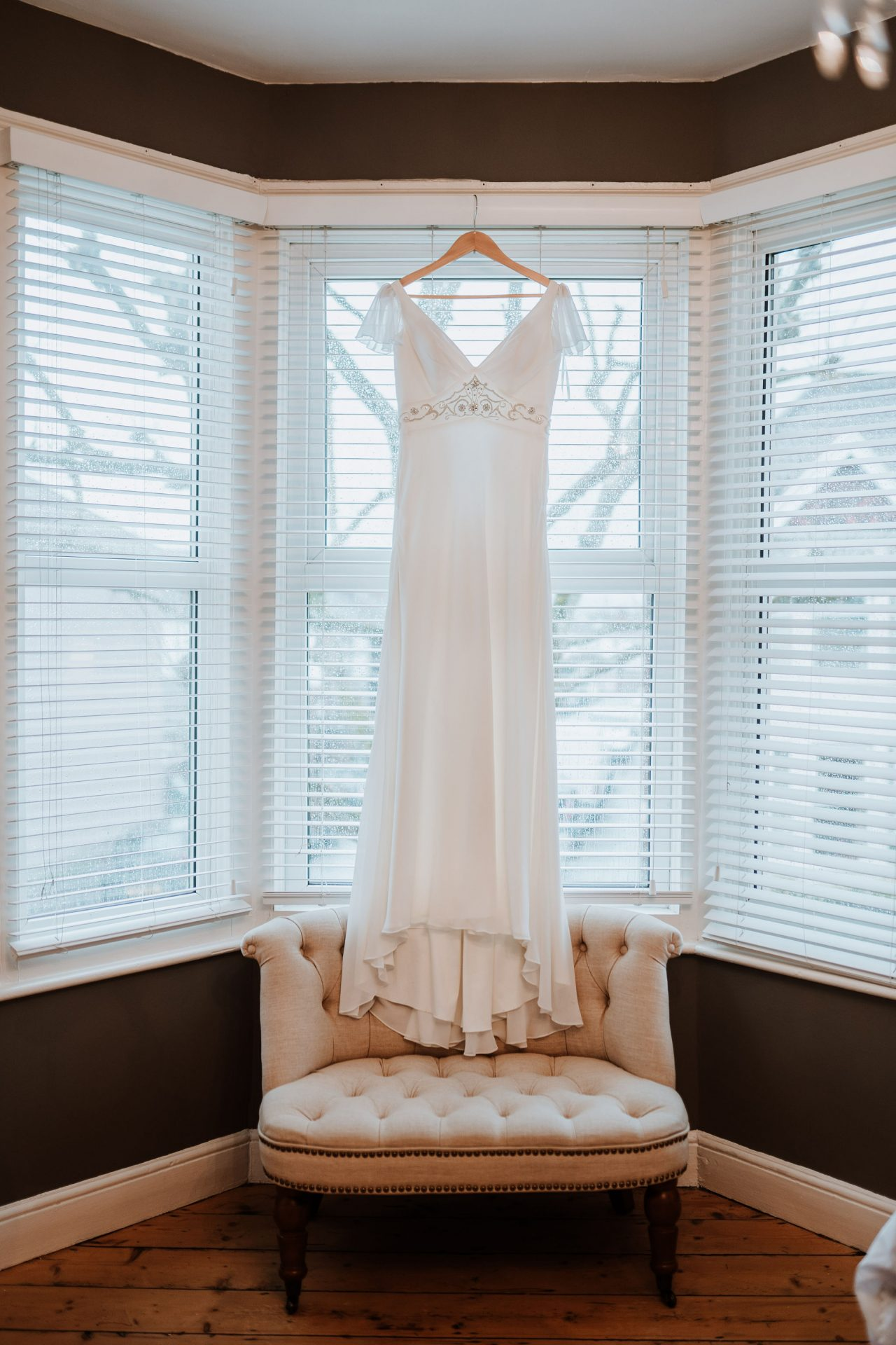 wedding dress hanging up in bay window