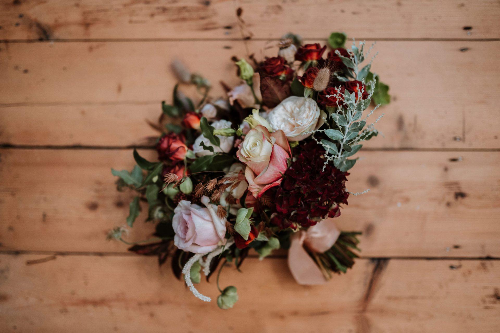 burgundy winter wedding bouquet on wooden floor