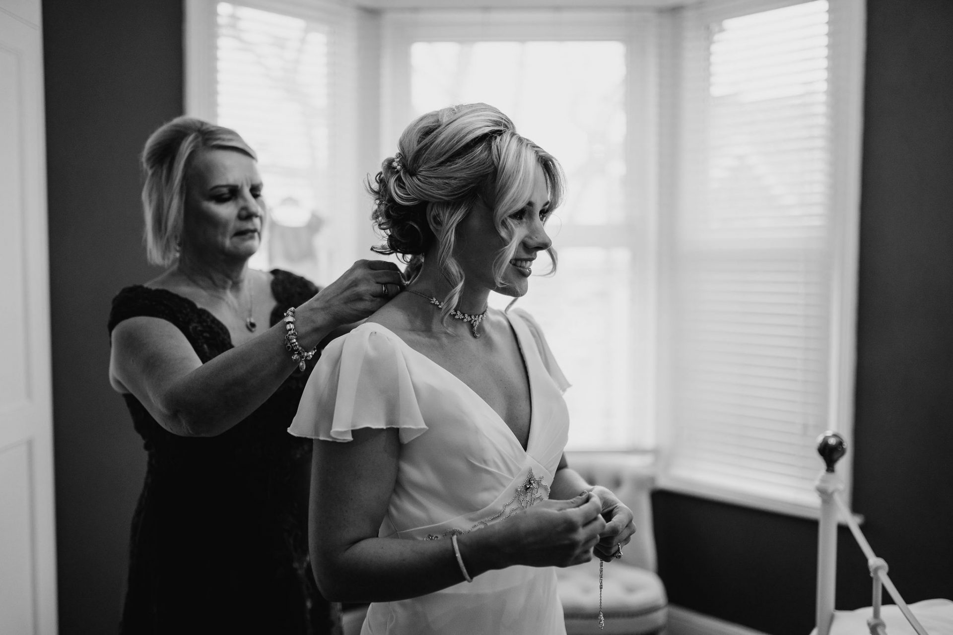 mother of the bride putting on the bride's necklace