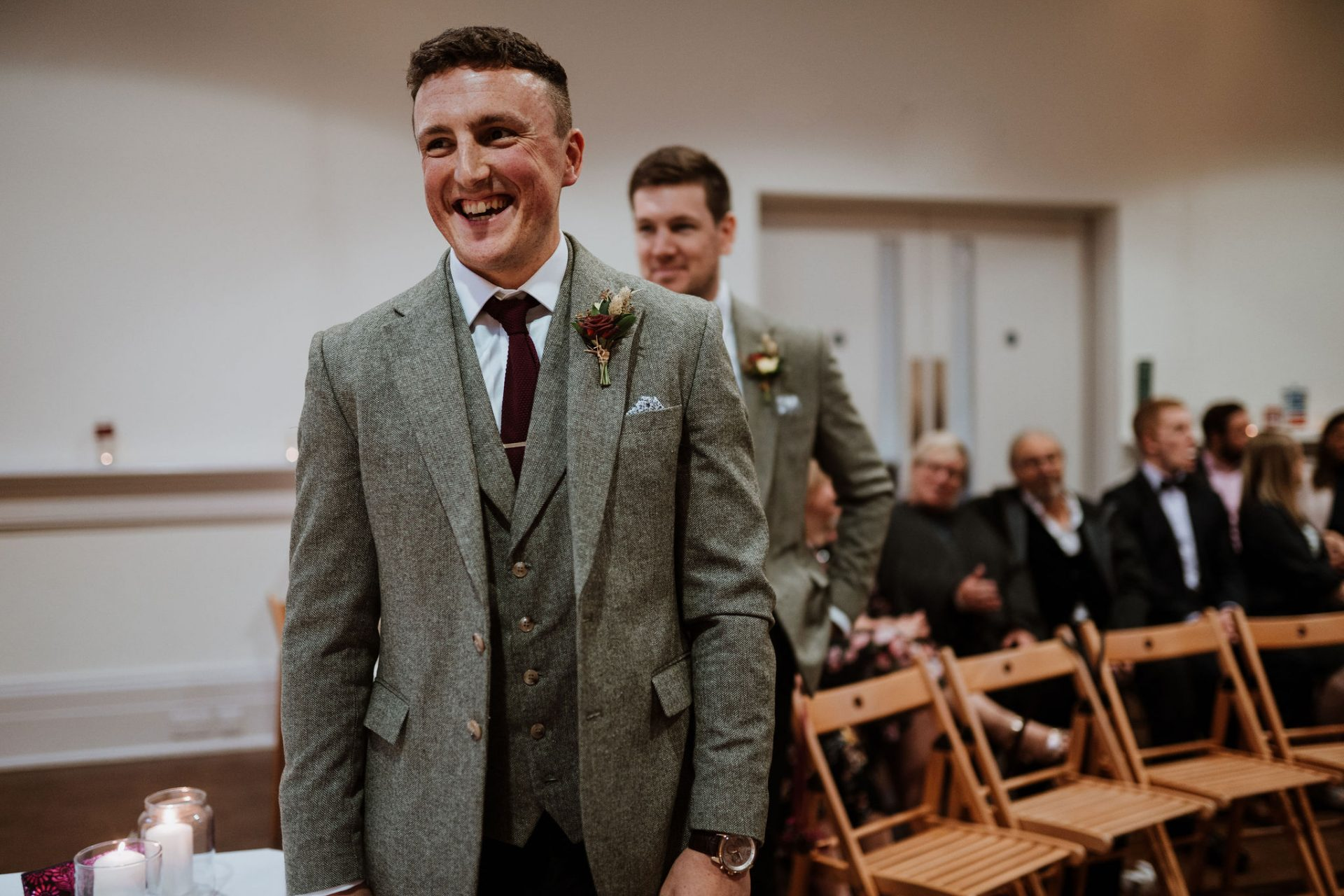 groom laughing in ceremony room