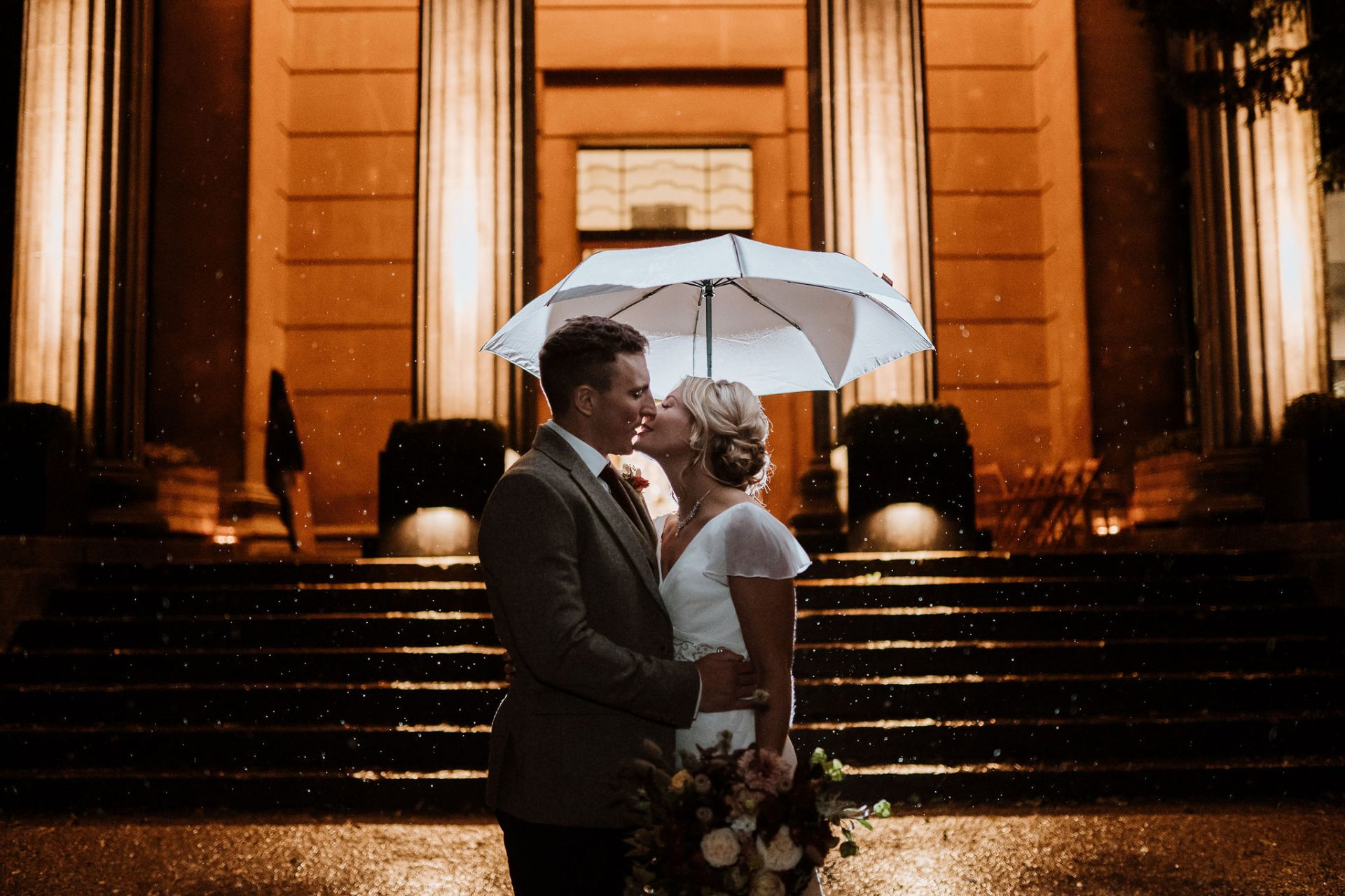 bride and groom in front of the spielman centre arnos vale backlit umbrella in the rain at night
