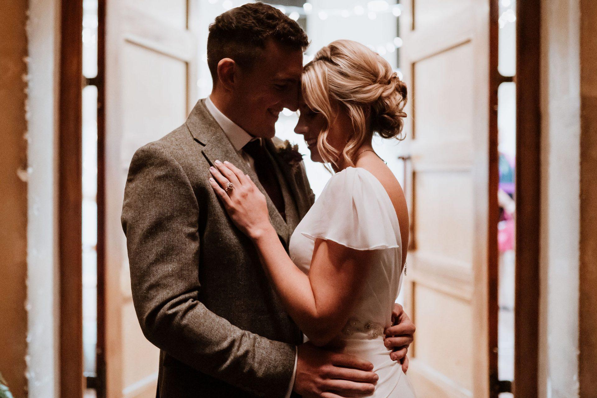 bride and groom hug foreheads together outside arnos vale