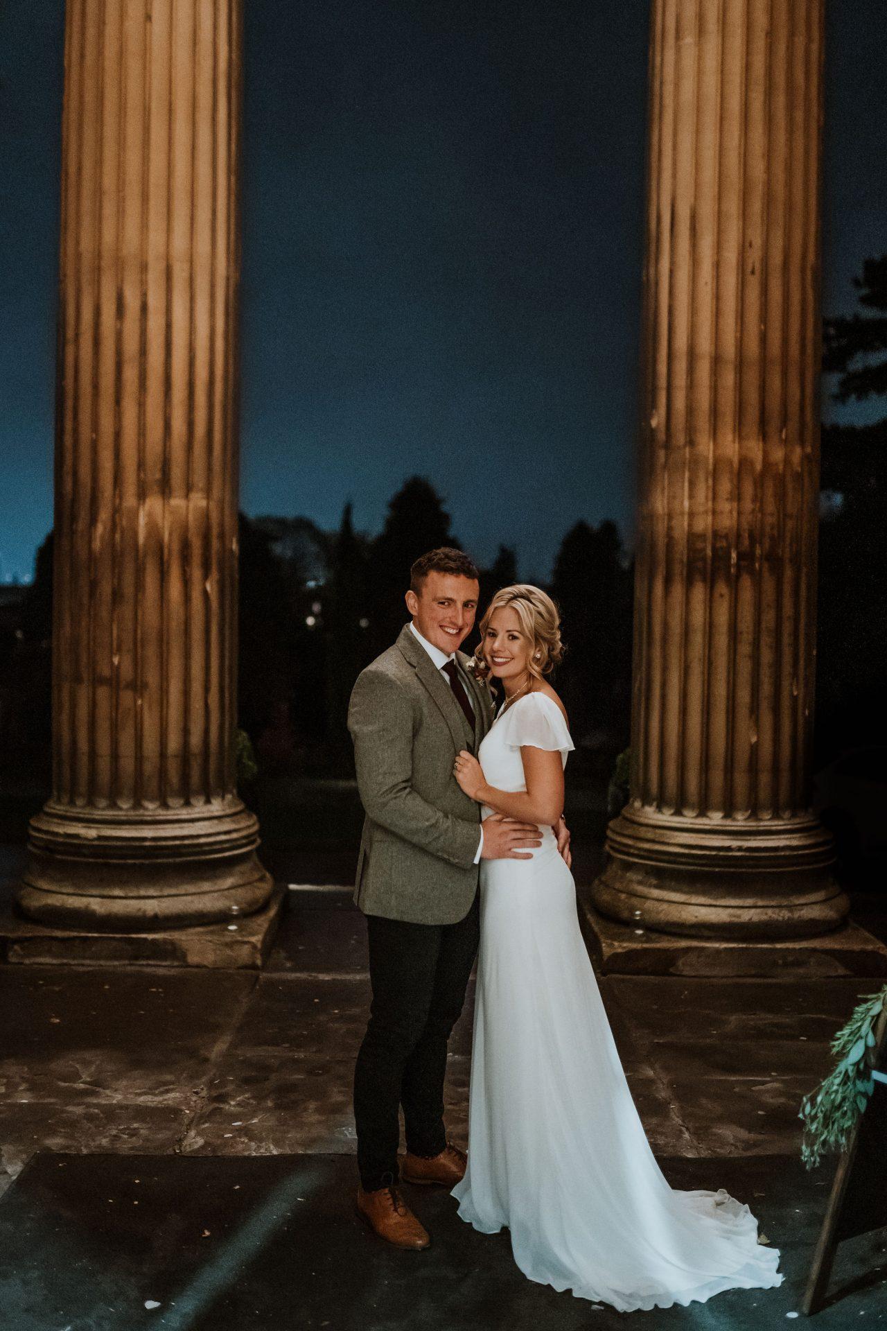bride and groom look at camera outside spielman centre arnos vale