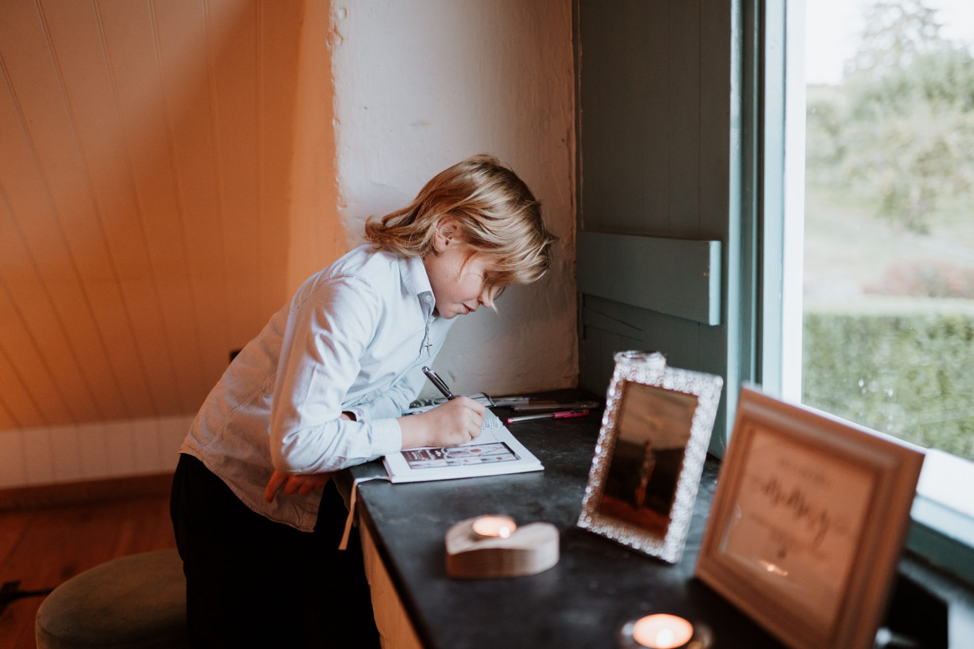 young boy writing in wedding guest book