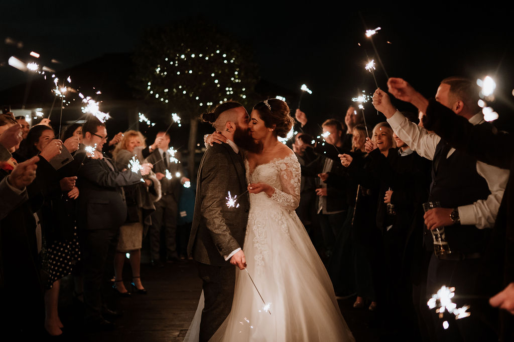 bride and groom kiss in sparkler tunnel