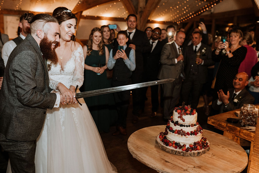 bride and groom cut naked cake with sword while guests watch