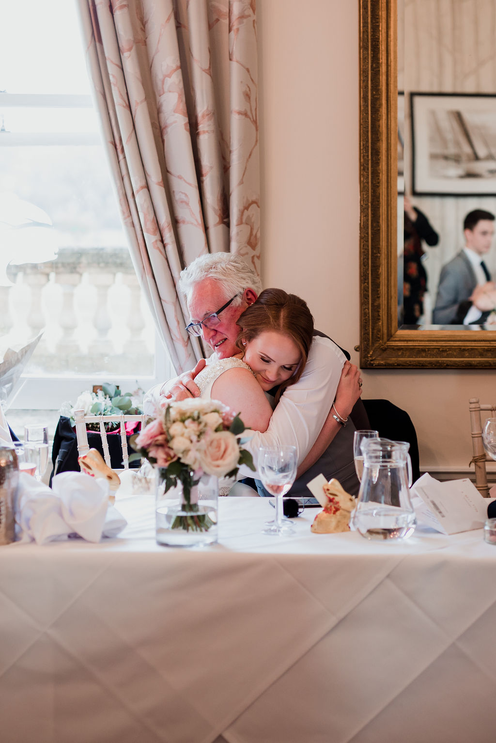 father hugs bride at top table