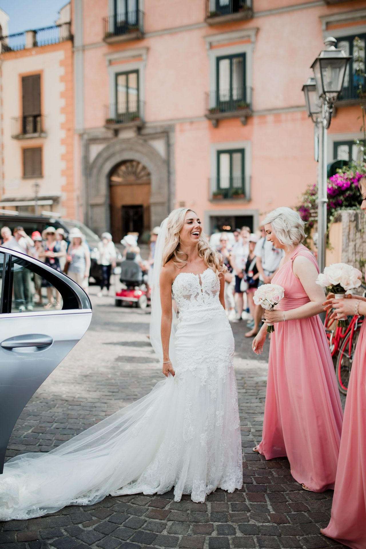 bride laughs getting out of wedding car
