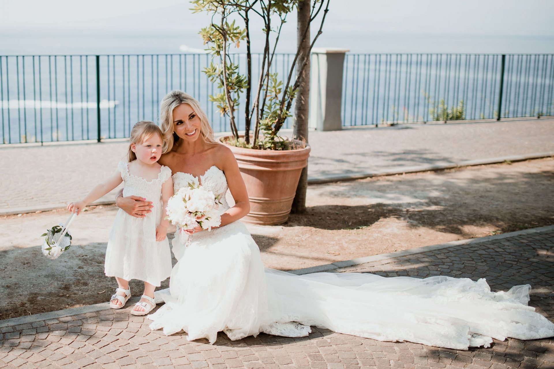 bride and flower girl pose in front of sea