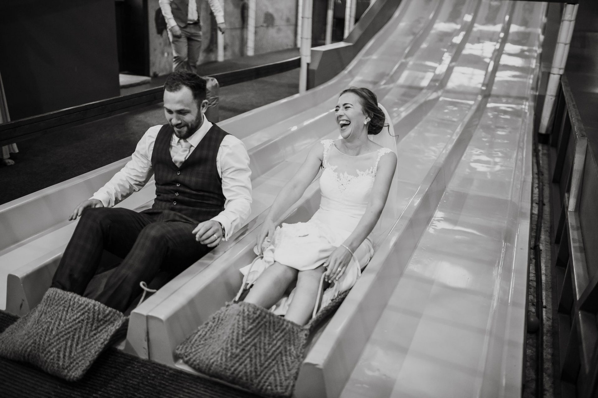 bride and groom go down a slide