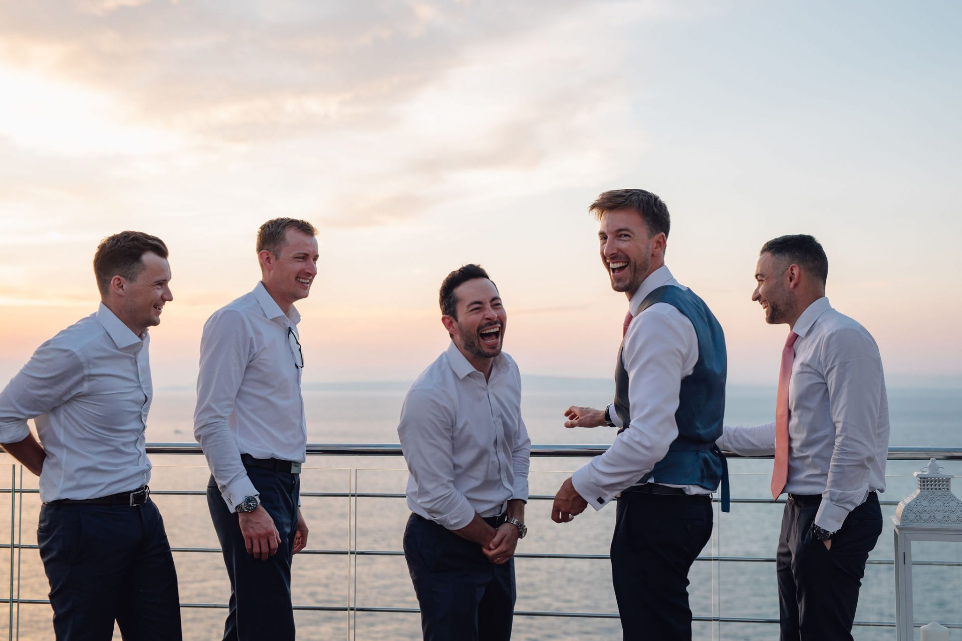 groom and groomsmen laughing at sunset sorrento