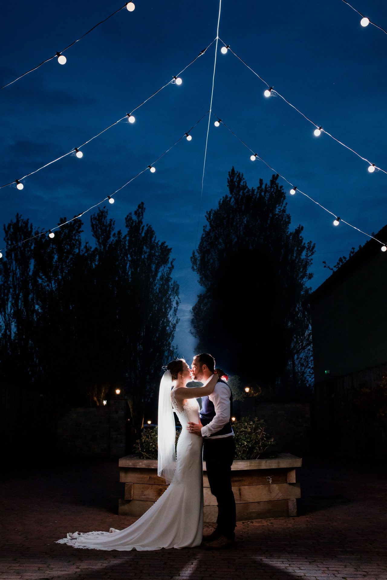 bride and groom kiss under fairy lights backlit barn at berkeley