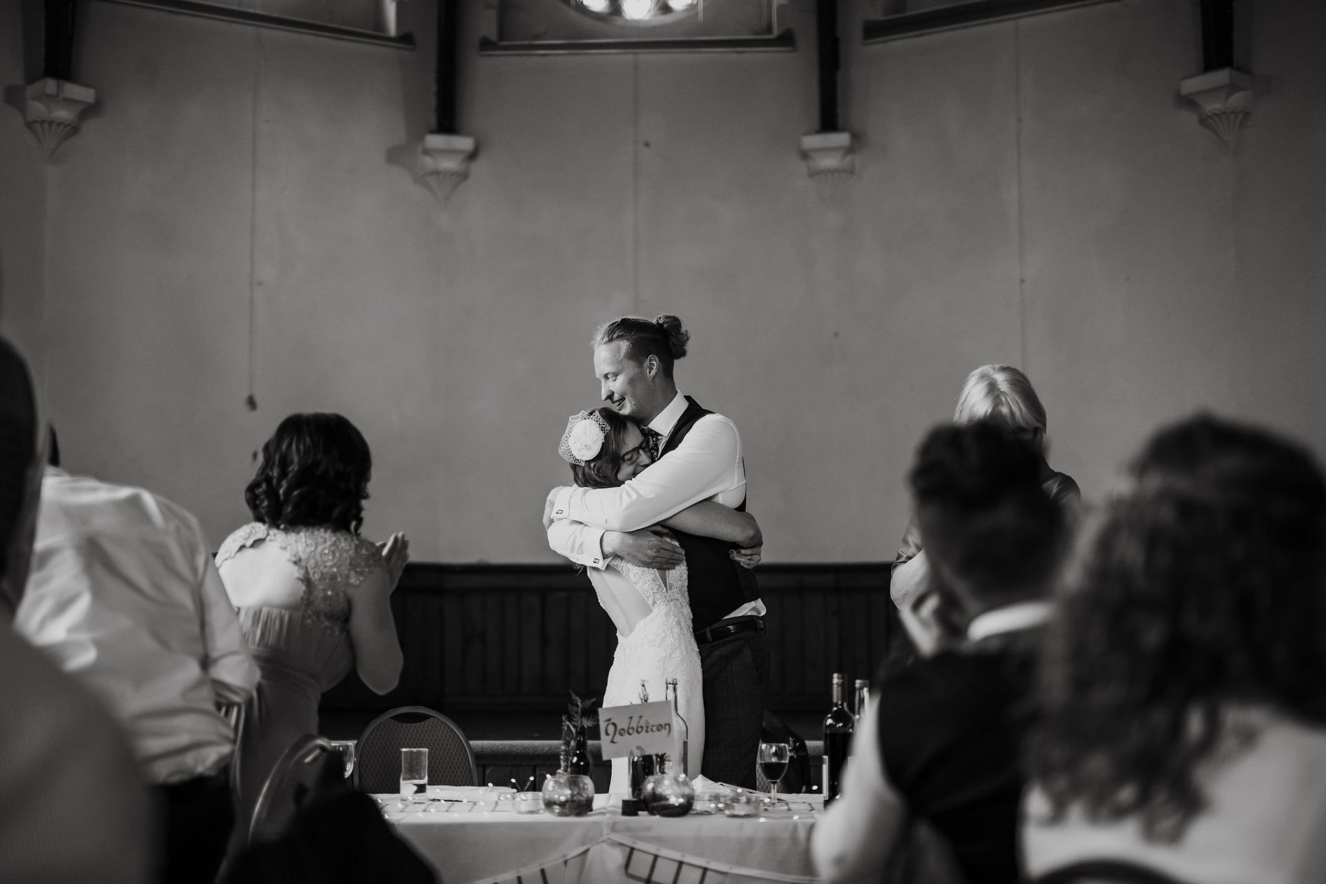 bride and groom hugging at the top table after wedding speeches