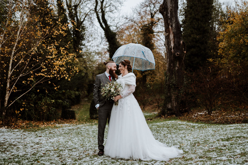 bride and groom stand on snow under clear umbrella