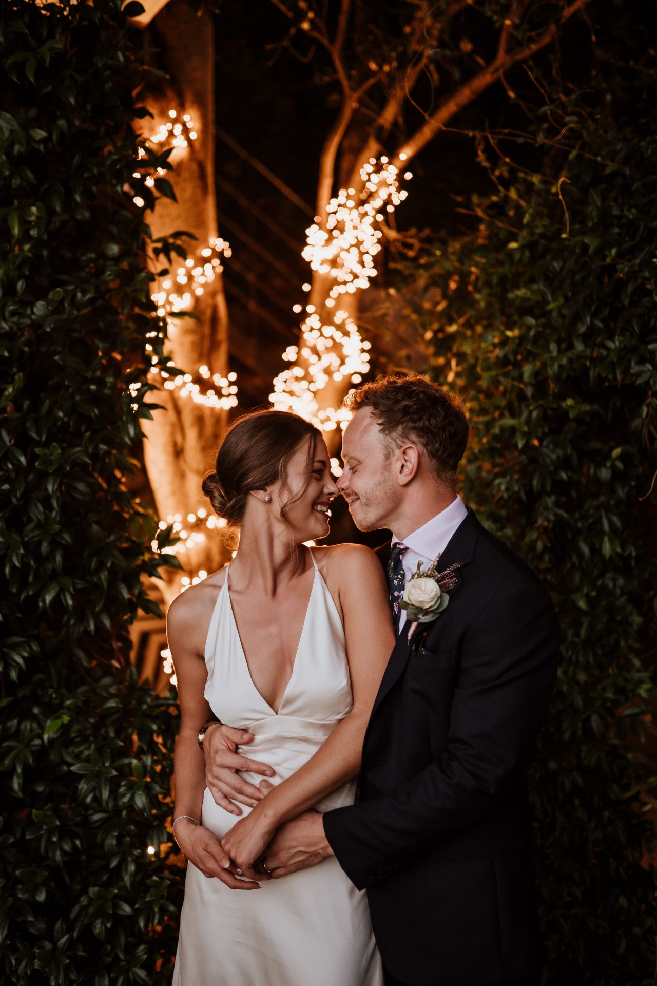 bride and groom touch noses in front of fairy lights